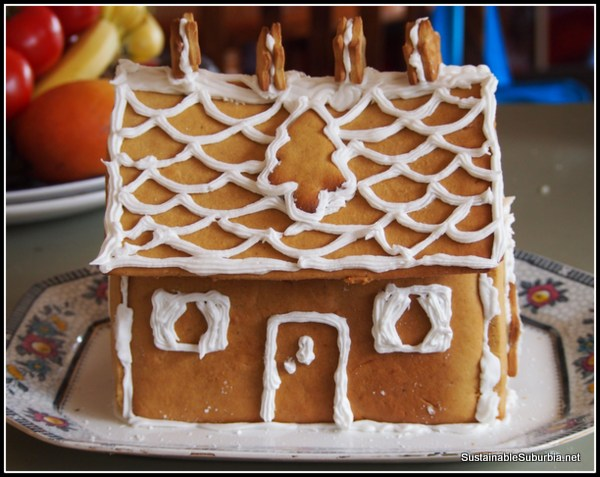 Gingerbread house decorated with white icing and ginger bread shapes.