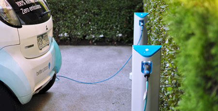 """car plugged in to a charging station with the words """"zero emissions"""" visible on the back"""