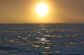 The sun sets over the melting artic sea ice