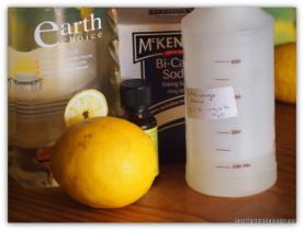 earth choice dish soap, a lemon, tea tree oil, baking soda and a spray bottle of homemade lemon citrus cleaner