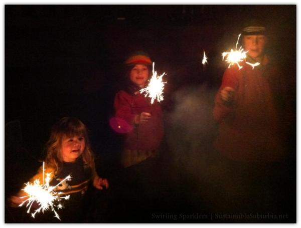 Three kids swirling sparklers in the dark