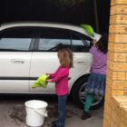 my kids cleaning my car with the Norwex car wash mitt and envirowand | SustainableSuburbia.net